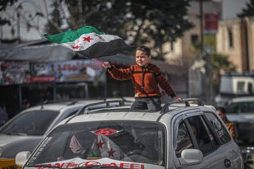 Civis sírios segurando estandartes e bandeiras, como o menino da foto, se reúnem para protestar pelo retorno à sua casa em Idlib , Síria em 19 de fevereiro de 2021. [Muhammed Said - Agência Anadolu]