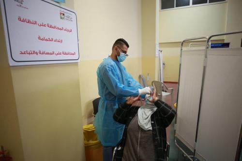 Trabalhador de saúde coleta uma amostra de esfregaço nasal de uma mulher para teste de coronavírus em Ramallah, Cisjordânia em 02 de março de 2021 [Agência Issam Rimawi / Anadolu]