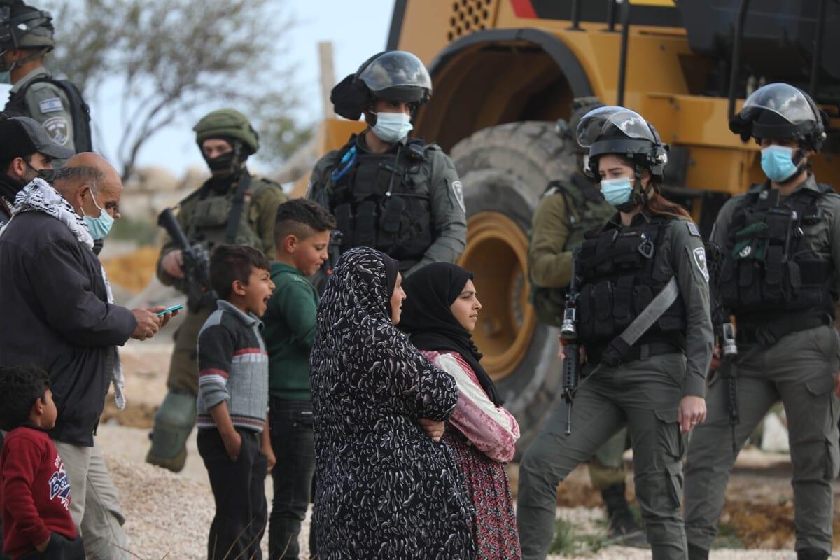 Crianças palestinas observam a demolição de suas casas por forças israelenses, em Hebron (Al Khalil), Cisjordânia ocupada, 2 de março de 2021 [Mamoun Wazwaz/Agência Anadolu]