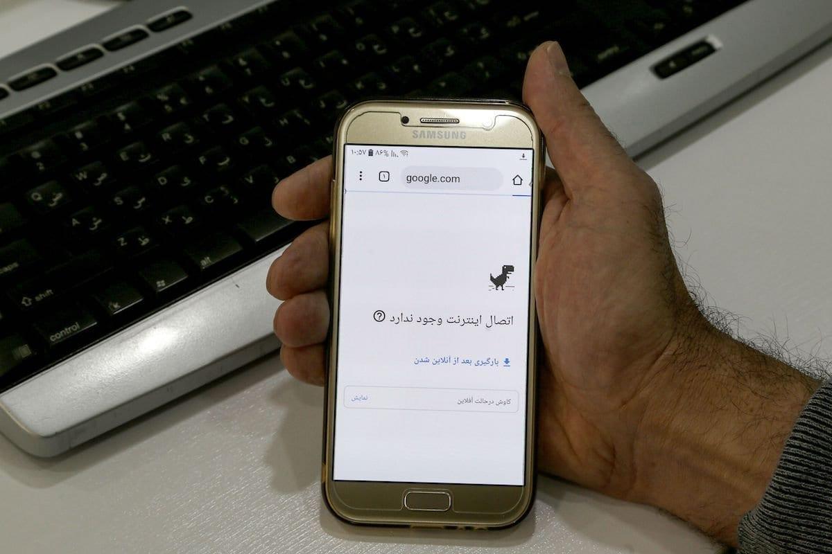 Um homem segura um smartphone conectado a uma rede Wifi sem acesso à Internet em um escritório na capital iraniana, Teerã, em 17 de novembro de 2019. [Atta Kenare/ AFP via Getty Images]