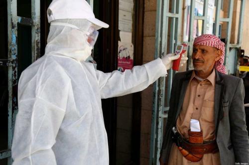 Um trabalhador médico mede a temperatura corporal de um homem em uma instalação estatal como medida de precaução para combater a covid-19, em 24 de março de 2020, em Sanaa, Iêmen. [Mohammed Hamoud/Getty Images]