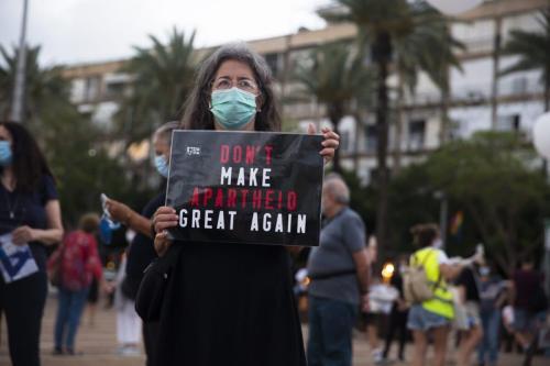 """Uma mulher israelense segura uma placa que diz """"Não torne o apartheid grande novamente"""" enquanto ela protesta contra o plano do governo de Israel, em 23 de junho de 2020, em Tel Aviv, Israel. [Amir Levy/Getty Images]"""