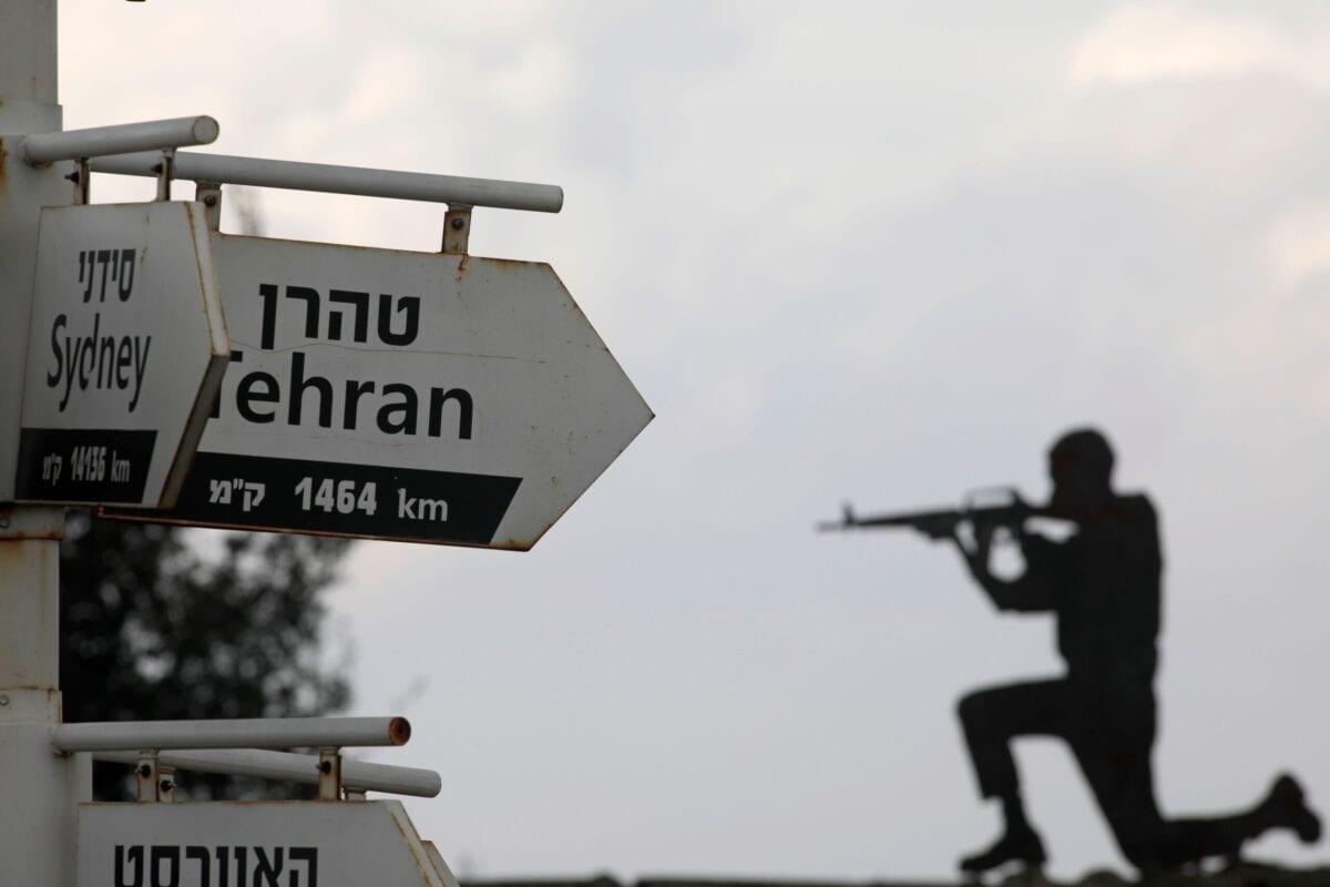 Recorte de um soldado israelense por trás de placas para diferentes cidades, no posto militar do Monte Bental, no território sírio ocupado das Colinas de Golã, em 28 de novembro de 2020 [Jalaa Marey/AFP via Getty Images]
