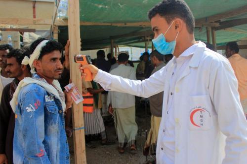 Um profissional de saúde verifica a temperatura de iemenitas deslocados em meio à pandemia de covid-19 em 12 de janeiro de 2021 [ Essa Ahmed/ AFP via Getty Images]