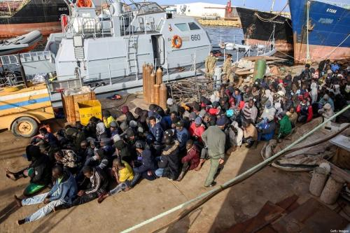 Migrantes resgatados na costa de Al-Khums, a cerca de 120 quilômetros a leste da capital, sentam-se no cais da base naval de Trípoli, em 10 de fevereiro de 2021. [AFP via Getty Images]
