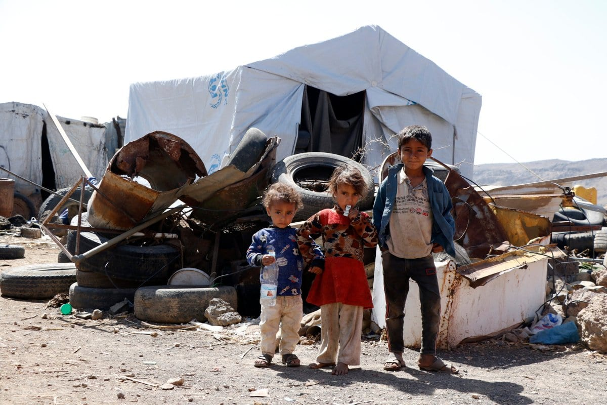 Crianças desalojadas devido à guerra em andamento ficam ao lado de barracas em um campo de deslocados internos, em 21 de fevereiro de 2021, na periferia de Sanaa, no Iêmen [Mohammed Hamoud/Getty Images]