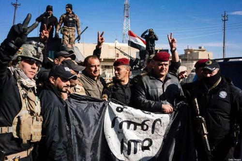 Membros do Serviço de Contraterrorismo do Iraque exibem uma bandeira do Estado Islâmico (Daesh) para celebrar uma vitória militar contra o grupo terrorista [Dimitar Dilkoff/AFP via Getty Images]