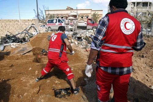 Membros do Crescente Vermelho Líbio exumam corpos não identificados de uma vala comum de pessoas mortas durante os combates na cidade da Líbia, Benghazi, para enterrá-los em um cemitério público, em 23 de fevereiro de 2017. [Abdullah Doma/AFP via Getty Images ]