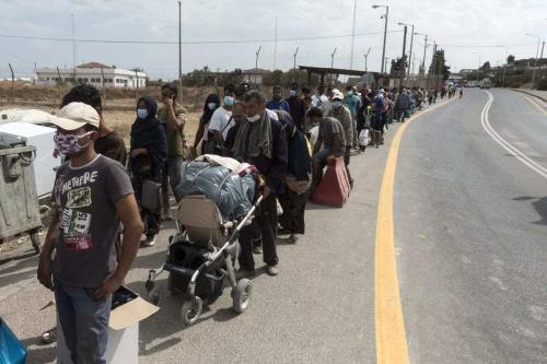 Refugiados esperam em uma fila na entrada de um campo temporário enquanto eles e seus pertences são verificados por policiais antes de se instalarem depois que o campo de refugiados de Moria se tornou inutilizável após os incêndios que eclodiram em 9 de setembro, na ilha grega de Lesbos, em 26 de setembro de 2020. [Ayhan Mehmet/Anadolu Agency]