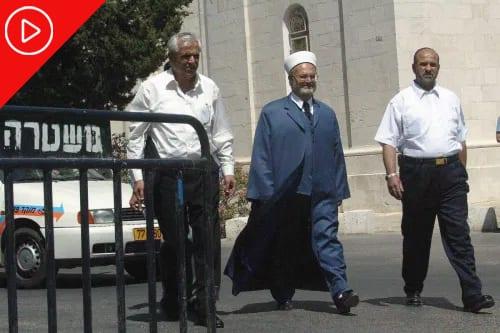 Mufti palestino de Jerusalém sheikh Ekrima Sabri (centro) chega a uma delegacia de polícia de Jerusalém para ser interrogado, em 17 de junho de 2003. [Atta Oweisat/AFP via Getty Images]