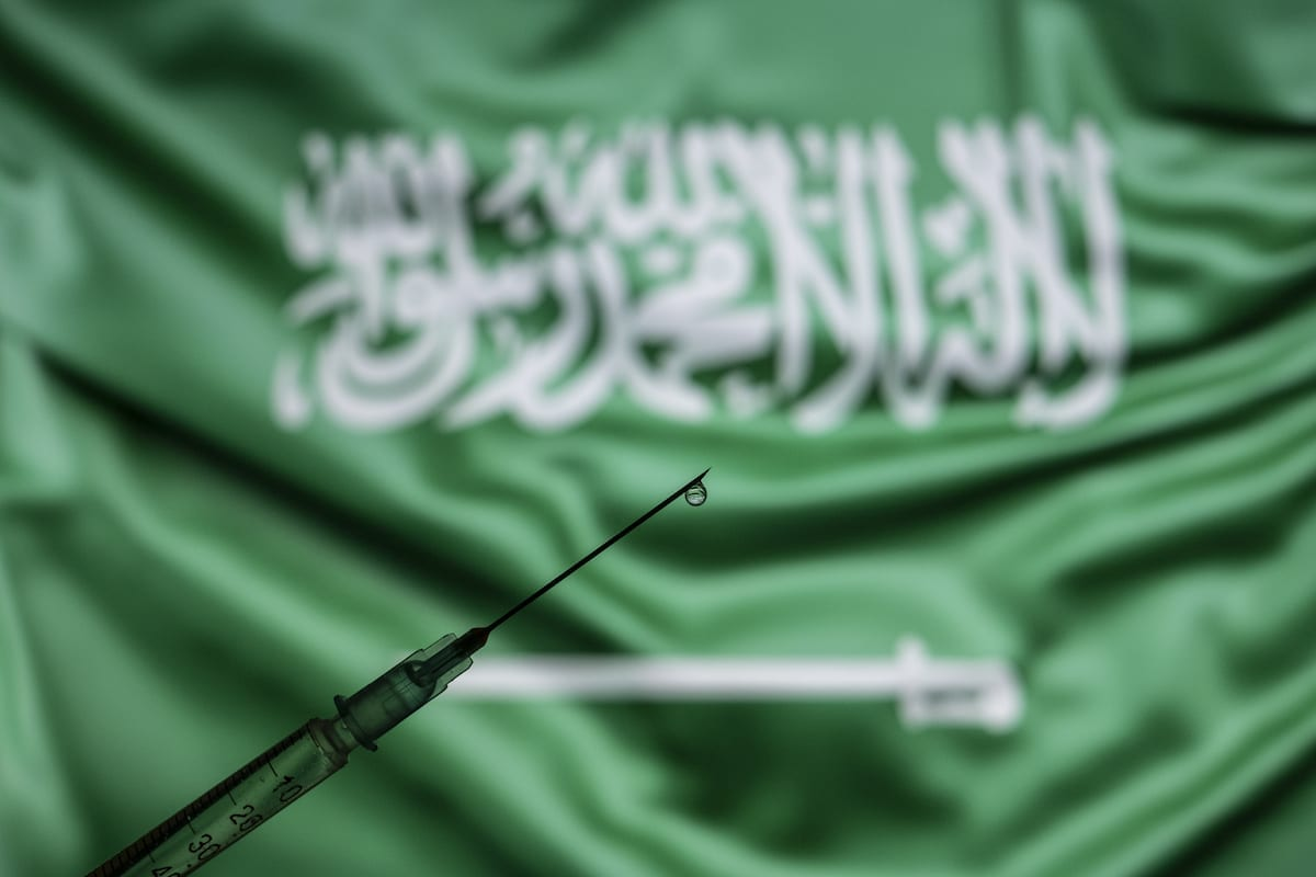Uma seringa de vacina com uma gota na ponta da agulha é vista na frente de uma tela de computador que mostra a bandeira nacional da Arábia Saudita. [Ali Balıkçı - Agência Anadolu]