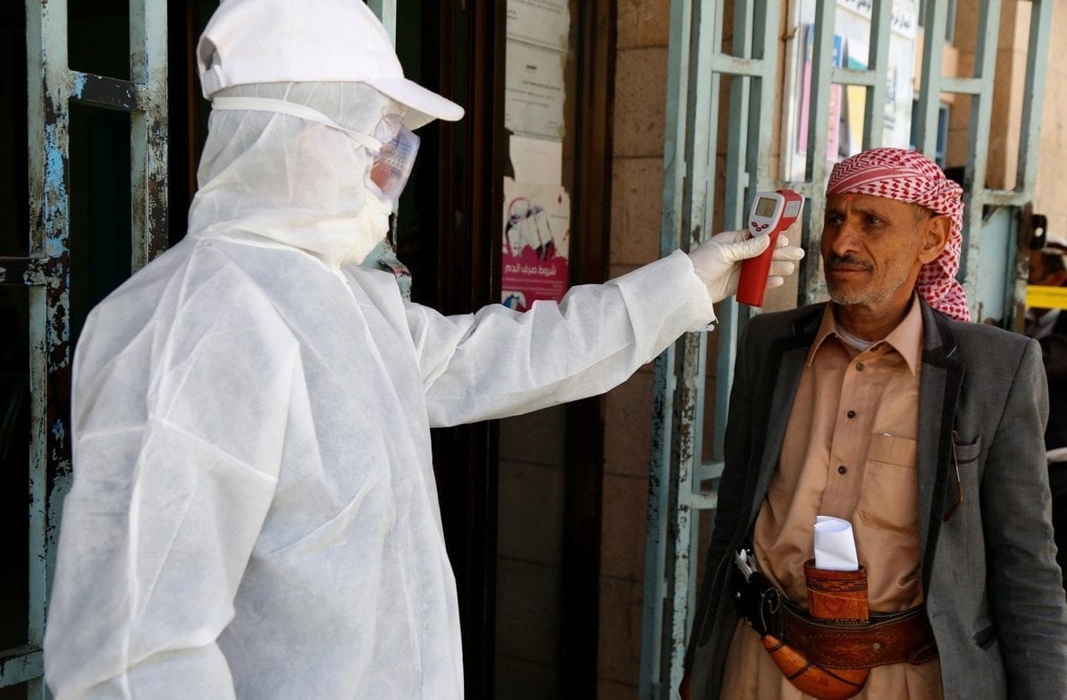 Trabalhador da área de saúde mede temperatura corporal de pacientes em uma instalação administrada pelo estado, como medida de prevenção para combater o coronavírus (covid-19), em Sanaa, Iêmen, 24 de março de 2020 [Mohammed Hamoud/Getty Images]