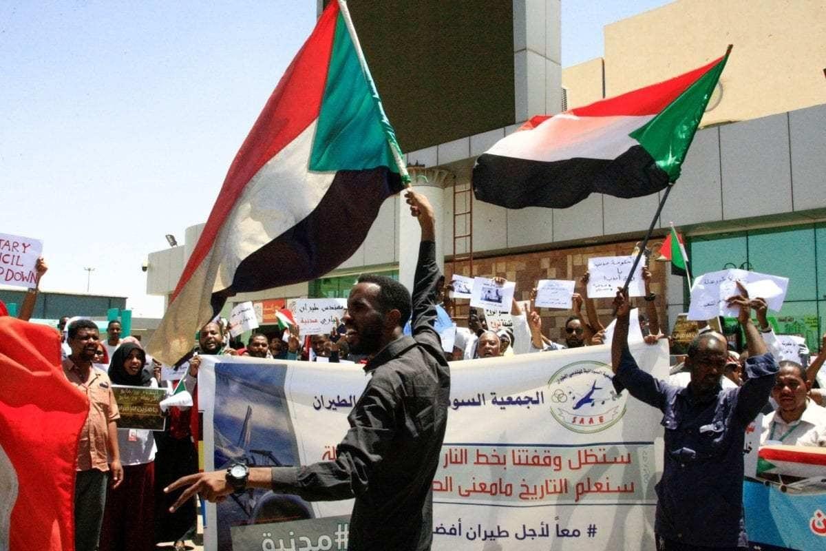 Trabalhadores do setor de aviação exibem bandeiras nacionais sudanesas em apoio ao governo civil, no aeroporto de Cartum, capital do Sudão, 27 de maio de 2019 [Ebrahim Hamid/AFP/Getty]