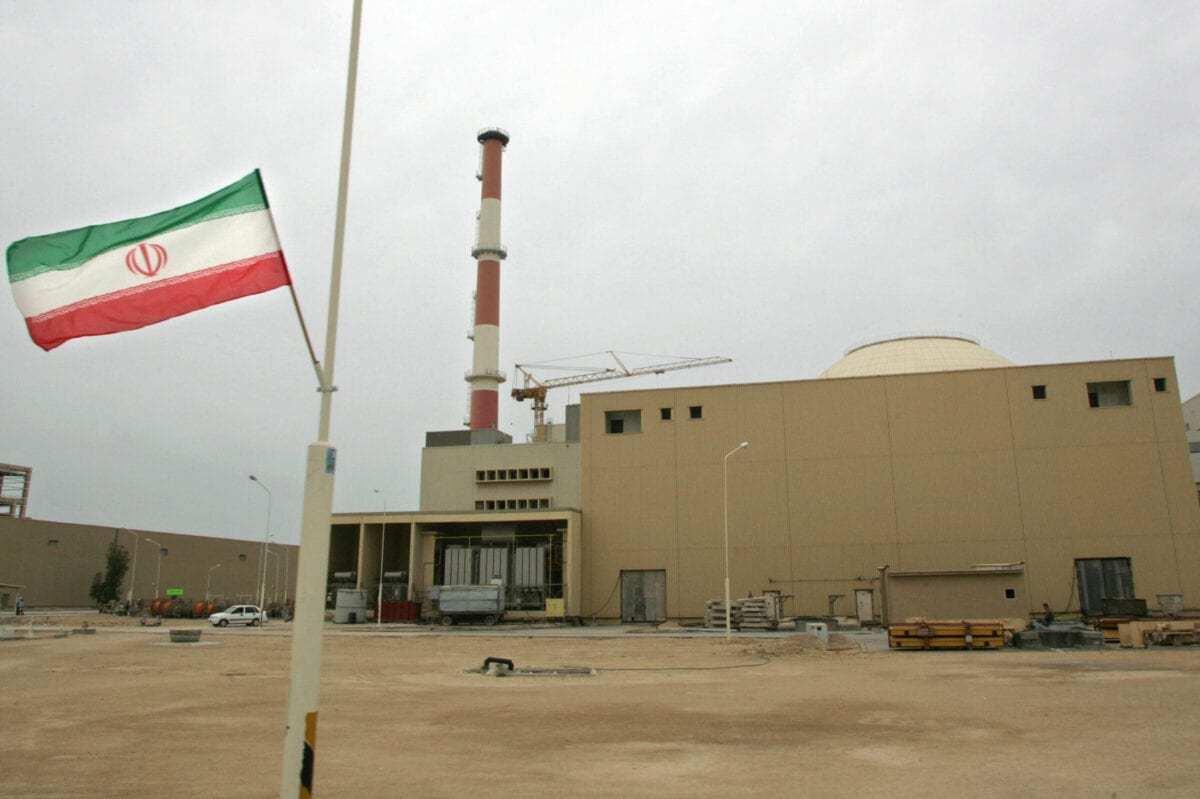Foto de arquivo datada de 3 de abril de 2007 mostra uma bandeira iraniana fora do prédio que abriga o reator da usina nuclear de Bushehr, na cidade portuária de Bushehr, no sul do Irã, 1200 km ao sul de Teerã. [Behrouz Mehri/AFP Files/AFP via Getty Images]