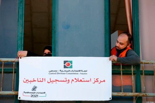 """Membros da Comissão Central Eleitoral Palestina instalam uma placa em árabe com os dizeres """"centro de registro e informações eleitorais"""", na cidade de Hebron (Al-Khalil), Cisjordânia ocupada, 10 de fevereiro de 2021 [Hazem Bader/AFP via Getty Images]"""