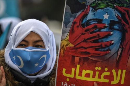 Membros da minoria Mulheres Muçulmanas Uigures seguram cartazes e bandeiras enquanto se manifestam, em 8 de março de 2021. [Ozan Kose/AFP via Getty Images]