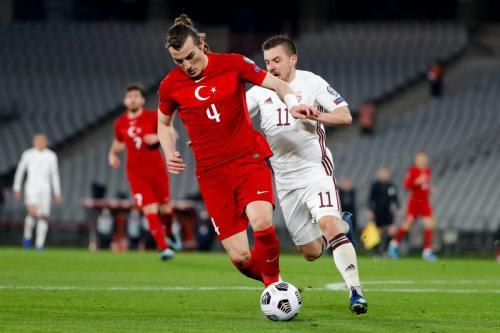 Caglar Soyuncu, da Turquia, e Roberts Savajnieks, da Letônia, durante a partida de qualificação da Copa do Mundo entre a Turquia e a Letônia no Estádio Olímpico Ataturk, em 30 de março de 2021, em Istambul, Turquia. [BSR Agency/Getty Images]