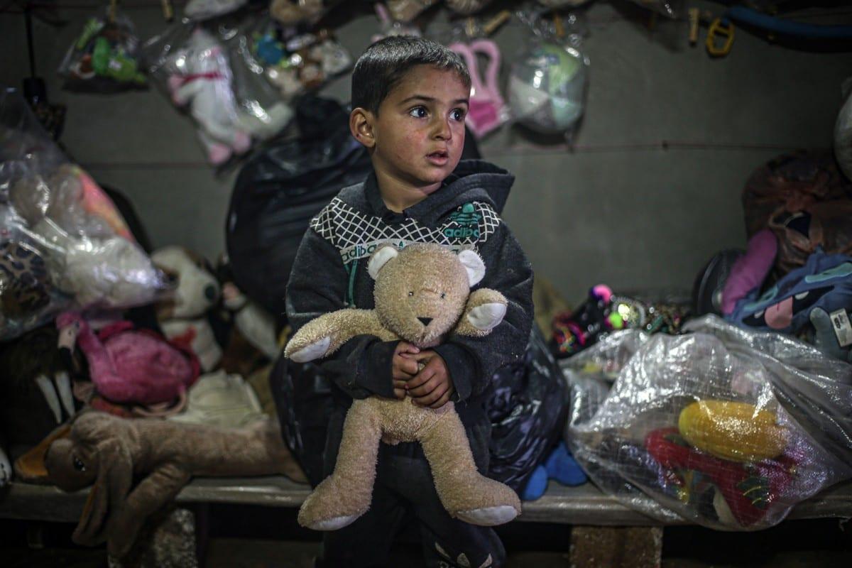 Uma criança síria segura um ursinho de pelúcia na loja de brinquedos infantis de Muhammed Kiteys, em um acampamento em Idlib, Síria, em 1º de fevereiro de 2021 [Muhammed Said/Agência Anadolu]