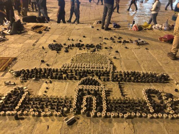"""Balas de borracha e granadas disparadas pela polícia israelense contra palestinos em Masjid al-Aqsa formam o desenho do Domo da Rocha e a palavra """"Al-Quds"""", em Jerusalém, 10 de maio de 2021 [Turgut Alp Boyraz/Agência Anadolu]"""