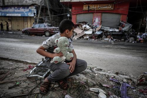 Um menino é visto com seu ursinho de pelúcia depois que sua casa foi danificada por ataques aéreos israelenses em Gaza em 19 de maio de 2021 [Ali Jadallah/Agência Anadolu]