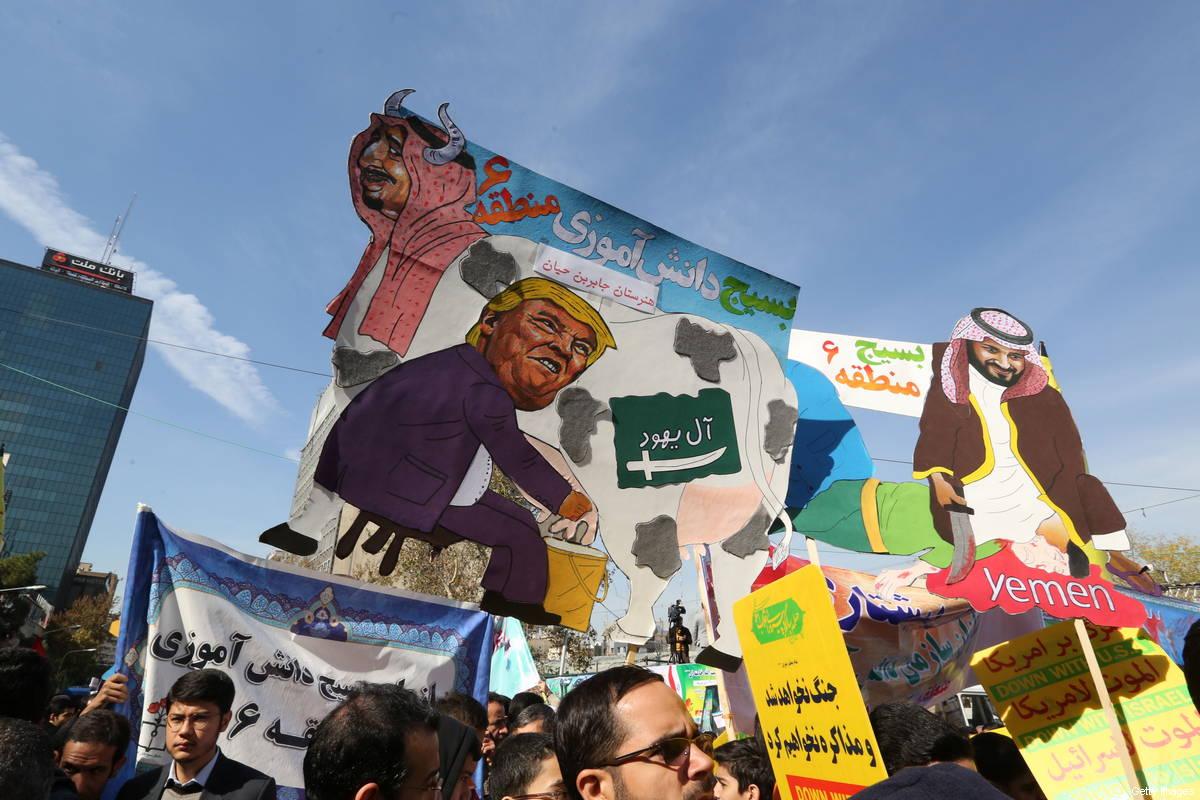 Na véspera da renovação das sanções por Washington, manifestantes iranianos carregam cartazes que zombam do presidente Donald Trump, do rei Salman da Arábia Saudita e do príncipe herdeiro Mohammed bin Salman durante uma manifestação em frente à ex-embaixada dos EUA na capital iraniana, Teerã, em 4 de novembro de 2018 [Atta Kenare/ AFP/ Getty Images]