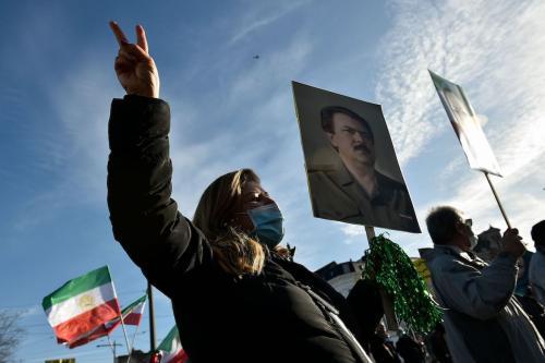 Pessoas agitam antigas bandeiras do Irã e seguram retratos enquanto protestam do lado de fora do tribunal de Antuérpia, em 4 de fevereiro de 2021, durante o julgamento de quatro suspeitos, incluindo um diplomata iraniano acusado de participar de um complô para bombardear uma manifestação da oposição na França. [John Thys/ AFP via Getty Images]