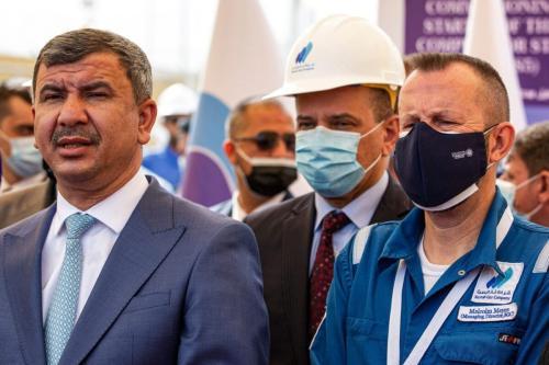 Ministro do Petróleo do Iraque Ihsan Abdul Jabbar (à esquerda) participa da inauguração de uma instalação de gás natural, ao lado de Malcolm Mayes, diretor administrativo da Basrah Gas Company (BGC), no campo de petróleo de Rumaylah, perto da cidade portuária de Basra, sul do Iraque, 28 de fevereiro de 2021 [Hussein Faleh/AFP via Getty Images]