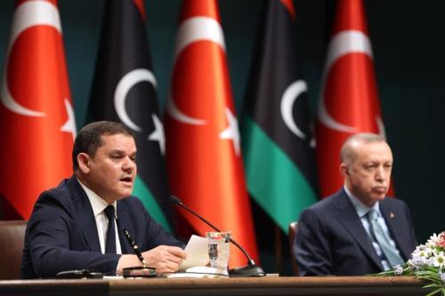 Presidente da Turquia Recep Tayyip Erdogan (à direita) e Primeiro-Ministro da Líbia Abdul Hamid Dbeibeh participam de cerimônia de assinatura de um acordo binacional, em Ancara, 12 de abril de 2021 [Adem Altan/AFP via Getty Images]
