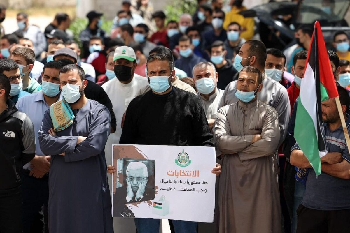 Apoiadores do movimento Hamas participam de uma manifestação contra a decisão do presidente da Autoridade Palestiniana de adiar as eleições legislativas e presidenciais marcadas para 22 de maio e 31 de julho, respectivamente, na Cidade de Gaza, em 30 de abril de 2021 [Mahmud Hams/AFP via Getty Images]