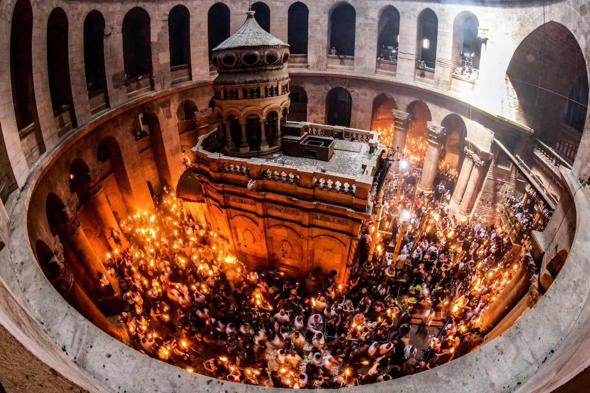 Cristãos ortodoxos reunidos acenderam velas ao redor do Edicule, que tradicionalmente se acredita ser o local do sepultamento de Jesus Cristo, durante a cerimônia do Fogo Sagrado na igreja do Santo Sepulcro de Jerusalém, em 1º de maio de 2021. [Emmanuel Dunand/ AFP via Getty Images]