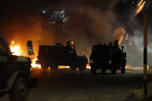 Soldados israelenses lançam gás lacrimogêneo contra manifestantes palestinos durante um protesto anti-Israel contra a tensão em Jerusalém, perto do assentamento judaico de Beit El perto de Ramallah, na Cisjordânia ocupada, em 12 de maio de 2021 [Abbas Momani/AFP via Getty Images]