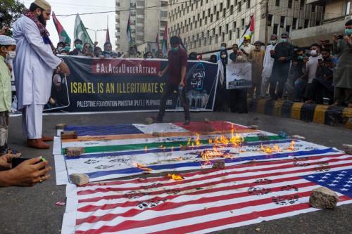 Manifestantes queimam bandeiras dos Estados Unidos, Israel, Índia e França durante protesto contra os ataques militares de Israel na Faixa de Gaza, em Karachi, Paquistão, 11 de maio de 2021 [Asim Hafeez/Bloomberg via Getty Image]