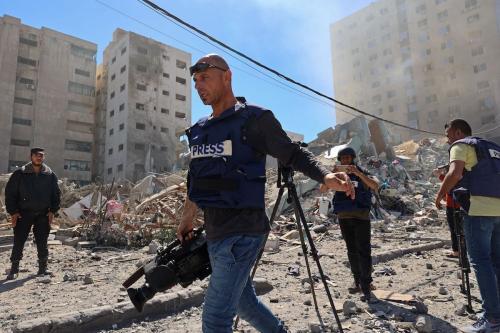 Jornalistas registram a destruição da Torre al-Jalaa, que abrigava escritórios da imprensa internacional, após ataques aéreos israelenses, na Faixa de Gaza, 15 de maio de 2021 [Mohammed Abed/AFP via Getty Images]