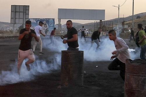 Manifestantes palestinos correm de bombas de gás lacrimogêneo durante protesto na Cisjordânia ocupada, 16 de maio de 2021 [Aafar Ashtiyeh/AFP via Getty Images]