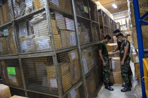 Soldados do Exército olham para caixas contendo anfetaminas e comprimidos ICE confiscados, em 23 de junho de 2017 [Roberto Schmidt/AFP via Getty Images)]