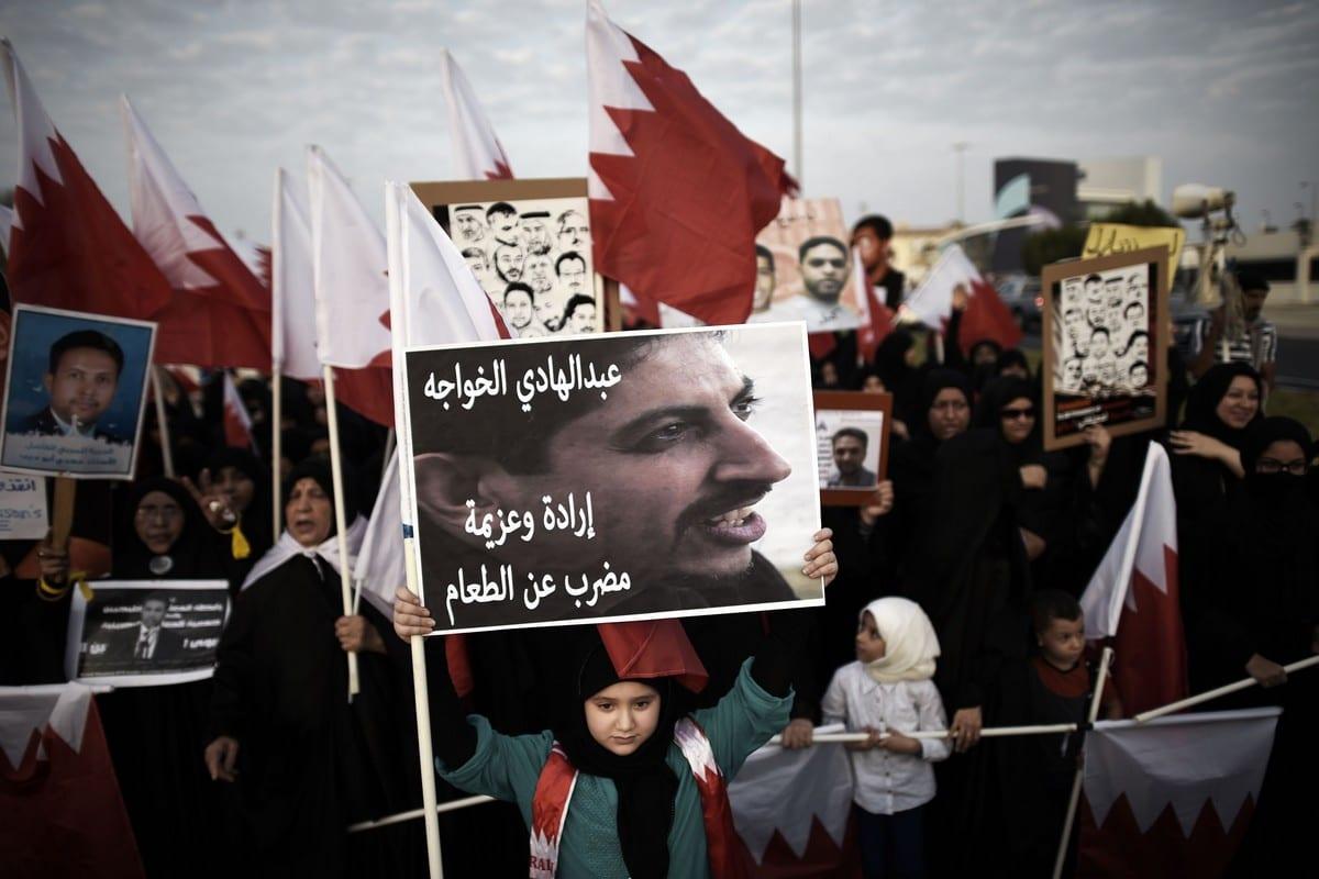 Uma menina do Bahrein segura um cartaz com um retrato do ativista de direitos humanos Abdulhadi Al-Khawaja em Manama, Bahrein, em 5 de setembro de 2014 [Mohammed Al-Shaikh/AFP/Getty Images]
