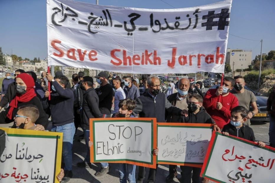 Ativistas palestinos, israelenses e estrangeiros exibem cartazes e faixas durante protesto contra a ocupação e os assentamentos de Israel nos territórios palestinos, no bairro de Sheikh Jarrah, em Jerusalém Oriental, 19 de março de 2021 [Ahmad Gharabli/AFP via Getty Images]