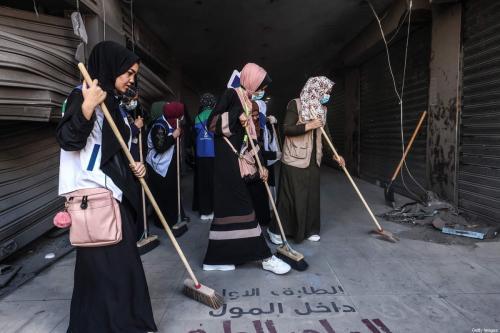 Voluntários limpam um beco no distrito comercial de Al-Remal na cidade de Gaza, recentemente alvo de ataques aéreos israelenses, em 23 de maio de 2021 [Emmanuel Dunand/AFP via Getty Images]