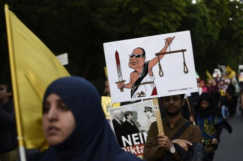 Um manifestante segura uma caricatura retratando o presidente egípcio Abdel Fattah al-Sisi como a Senhora da Justiça com uma espada ensanguentada e balanças de forca durante uma manifestação contra a política do presidente egípcio, em 3 de junho de 2015, perto da embaixada egípcia em Berlim [Odd Andersen/AFP via Getty Images]
