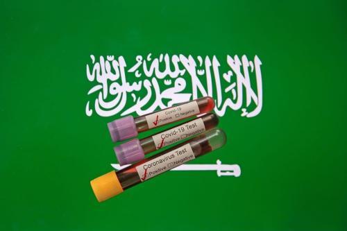 Nesta ilustração fotográfica, amostras positivas de sangue para coronavírus (covid-19) são vistas em frente a uma tela de computador com a bandeira da Arábia Saudita [Mehmet Emin Mengüarslan / Agência Anadolu]