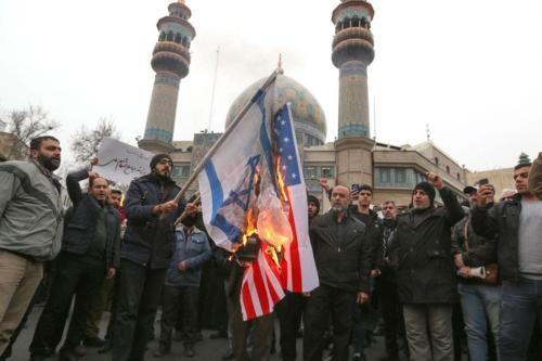 Iranianos queimam bandeiras dos EUA e de Israel durante um protesto contra os assassinatos do comandante militar iraniano Qasem Soleimani e do chefe paramilitar iraquiano Abu Mahdi al-Muhandis durante um ataque aéreo americano, na capital Teerã, em 4 de janeiro de 2020 [ATTA KENARE/AFP via Getty Images]