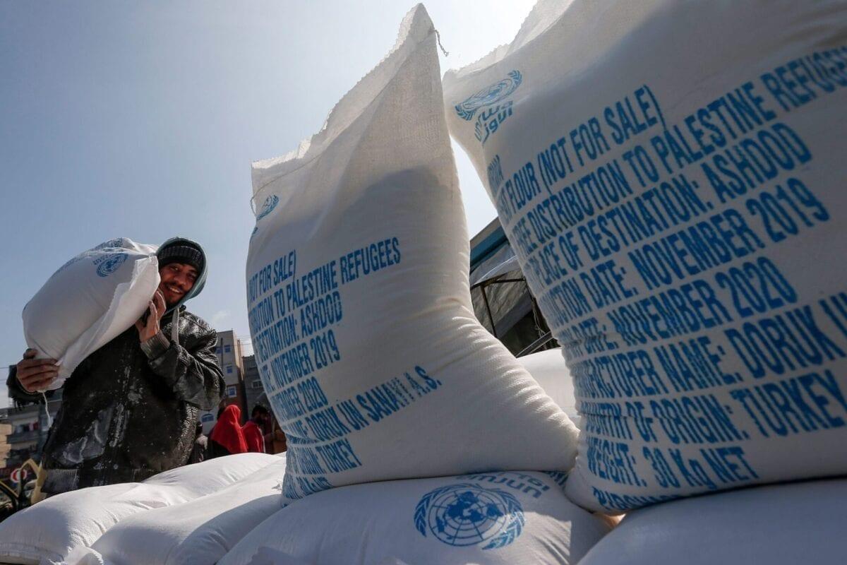 Palestino carrega um saco de farinha sobre os ombros, após a chegada de doações da Agência das Nações Unidas de Assistência aos Refugiados da Palestina (UNRWA), no campo de refugiados de Jabalia, norte da Faixa de Gaza, 29 de janeiro de 2020 [Mahmud Hams/AFP via Getty Images]