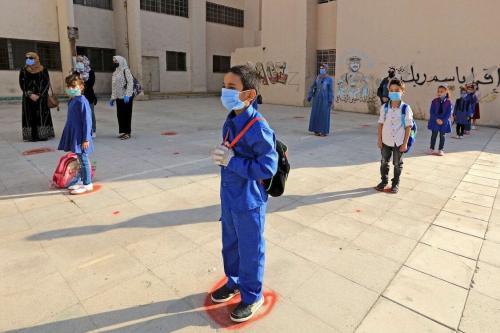 Estudantes com máscara e distanciamento social em uma escola de Amã, capital da Jordânia, durante a pandemia de covid-19, em 1° de setembro de 2020 [Khalil Mazraawi/AFP via Getty Images]