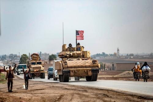 Crianças gesticulam a um comboio militar dos Estados Unidos, nos arredores da aldeia de al-Jawadiyah, na província de Hasakeh, nordeste da Síria, perto da fronteira com a Turquia, em 17 de dezembro de 2020 [Delil Souleiman/AFP via Getty Images]