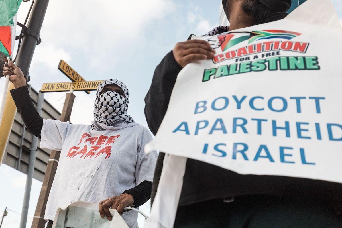 """Os partidários pró-Palestinos seguram cartazes com a leitura """"Boicote ao Apartheid Israel"""" durante um protesto para condenar os ataques aéreos israelenses em andamento em Gaza, em Durban, em 18 de maio de 2021 [RAJESH JANTILAL/AFP via Getty Images]"""