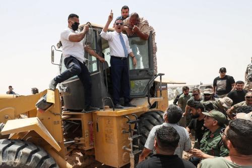 Abdulhamid Dbeibah, primeiro-ministro interino líbio, acena no topo de uma escavadeira em 20 de junho de 2021, na cidade de Buwairat al-Hassoun, durante uma cerimônia para marcar a reabertura de uma estrada de 300 km entre as cidades de Misrata e Sirte. [MAHMUD TURKIA/AFP via Getty Images]