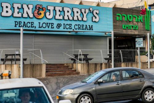"""Os motoristas passam por uma sorveteria """"Ben&Jerry's"""" fechada na cidade israelense de Yavne, cerca de 30 quilômetros ao sul de Tel Aviv, em 23 de julho de 2021 [Ahmad Gharaabli/AFP via Getty Images]"""