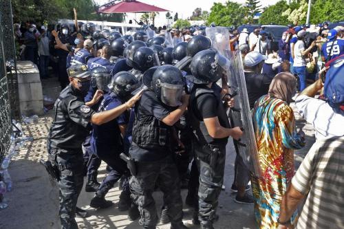 Agentes de segurança tunisianos seguram manifestantes em frente ao prédio do parlamento na capital Túnis, em 26 de julho de 2021, após uma ação do presidente para suspender o parlamento do país e demitir o primeiro-ministro [Fethi Belaid/AFP via Getty Images]