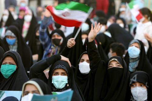 Apoiadores do então candidato presidencial Ebrahim Raisi segurando bandeiras iranianas e as fotos dele se reúnem durante um comício antes das eleições presidenciais iranianas a serem realizadas em 18 de junho, na Praça Hafte Tir em Teerã, Irã, em 14 de junho de 2021 [Fatemeh Bahrami/Agência Anadolu]