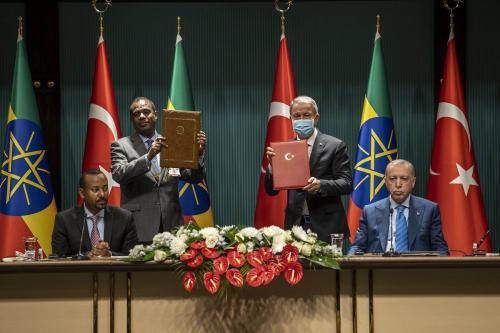 Presidente da Turquia Recep Tayyip Erdogan (à direita) e Primeiro-Ministro da Etiópia Abiy Ahmed (à esquerda) acompanham assinatura de acordo bilateral; de pé, seus respectivos ministros da defesa Hulusi Akar e Keana Yadeta, em Ancara, 18 de agosto de 2021 [Ali Balikçi/Agência Anadolu]